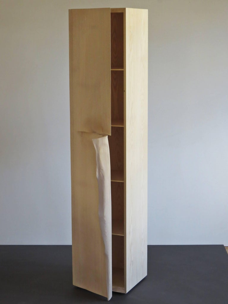 Tall cabinet handmade from solid ashwood. Created by the German furniture maker and sculptor Eckehard Weimann. A classic rectilinear body is broken by a grip like a dog's ear. Sculpted, this handle looks like a kinky paper. Surface oiled