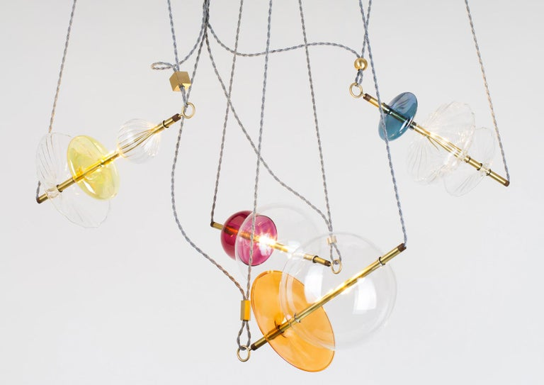 The Trapezi is a single edition, one of a kind pendant light or chandelier, inspired by the idea of a Circus Trapeze Artist. This unusual light pendant composition reinterprets in a totally different way the classic Murano chandelier
