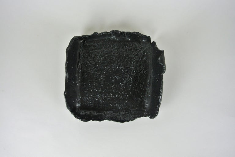 Rough grey stoneware tray with visible fire sand texture on surface. Glazed with black silvery glaze. Asymmetric shape and raw edges. Functional or for decoration