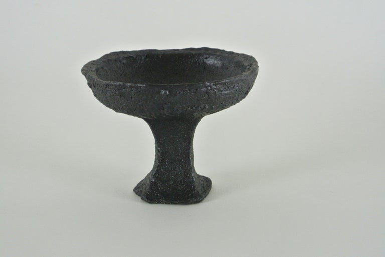 Black, rough stoneware goblet with black metallic glaze. Slightly asymmetric shape and visible fire sand structure on the surface.