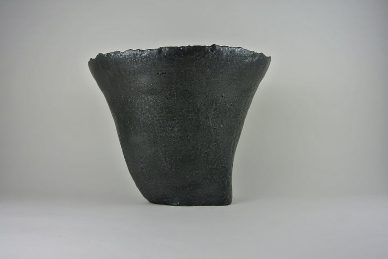 Massive asymmetric vessel in grey, rough stoneware with black metallic glaze. Fire sand texture visible on surface. Available with or without flower tray. All pieces by Christine Roland celebrate the imperfections that occur from working with a