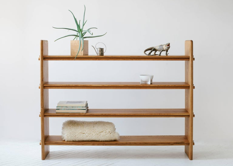 Designed with a focus on traditional joinery, there is not a single piece of metal hardware used in these white oakwood shelves. Small wooden wedges are used to hold the shelves captive between the vertical sides through sheer tension.