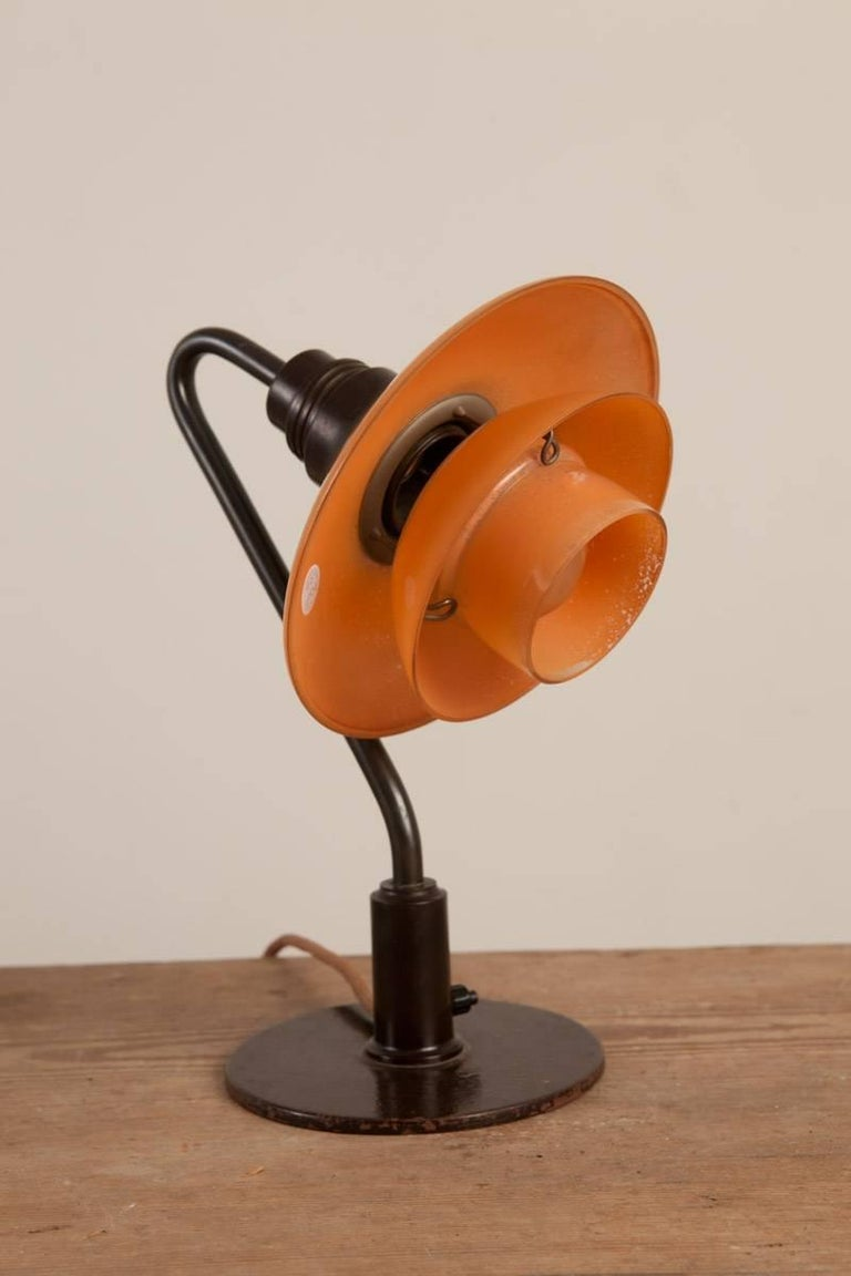 Poul Henningsen (1894 Ordrup, Denmark 1967) Early, low miniature table lamp with 2/2 red frosted glass shades Patinated metal parts, brown bakelite Manufactured by Louis Poulsen, Copenhagen, Denmark, Circa 1933  Literature: Light Years Ahead, The