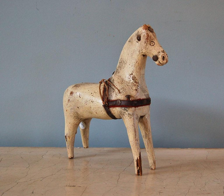 A Swedish 18th century dala horse, origin: Sweden, circa 1750.  Hand-carved horse, from one piece of wood, including charming carved details such as the eyes and nose; original 18th century paint and remnants of original leather and red fabric