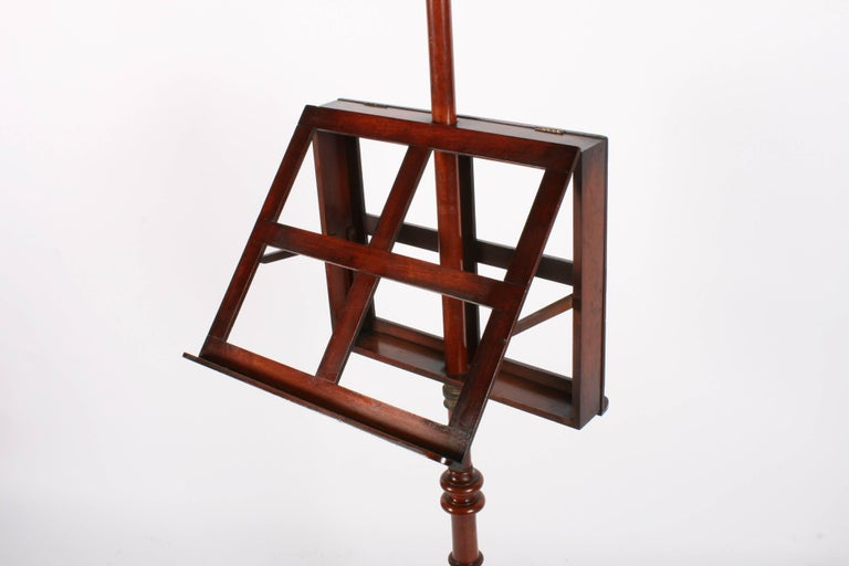 Victorian mahogany duet music stand, circa 1870. With urn shaped top on a large column, there is an adjustable frame with brass collar on mahogany arms. The turned column continues down to a large central block before leading on to cabriole legs on