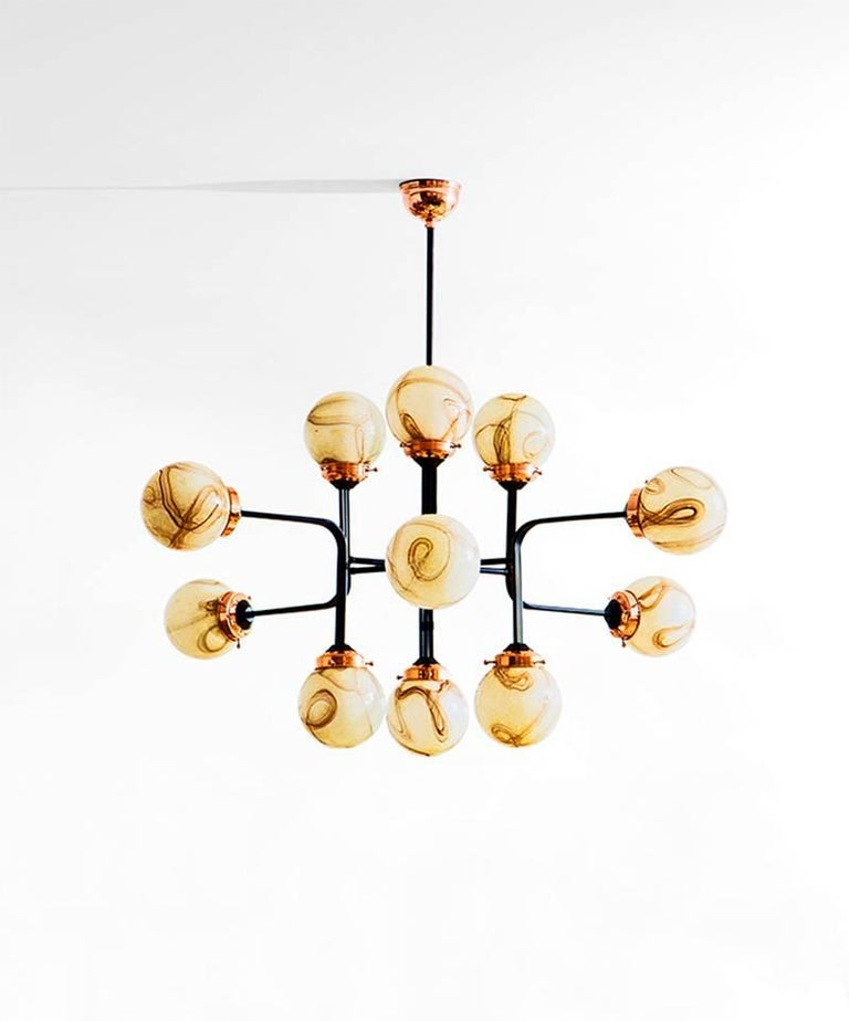 Ziron is an entirely handmade chandelier inspired by antique handblown glasses, which are not produced anymore. Each handblown glass dome is unique with different patterns but harmonize with each other in an elegant way. Black painted metal pieces