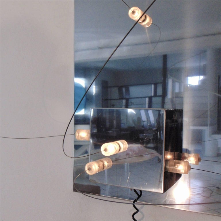 Low-voltage, modular, sculptural small wall lamp in stainless steel with eight lights with magnetic, movable perspex cylinders and a movable cube, that can be detached from the main board and repositioned with ease in any part of the main