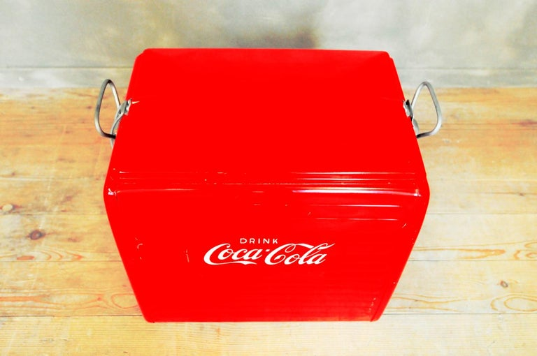 This Coca Cola cooler was bought in the USA in the 1950s or 1960s and brought to Europe. The aluminum box is meant to be filled with ice cubes to keep drinks cool. The top clamps shut.