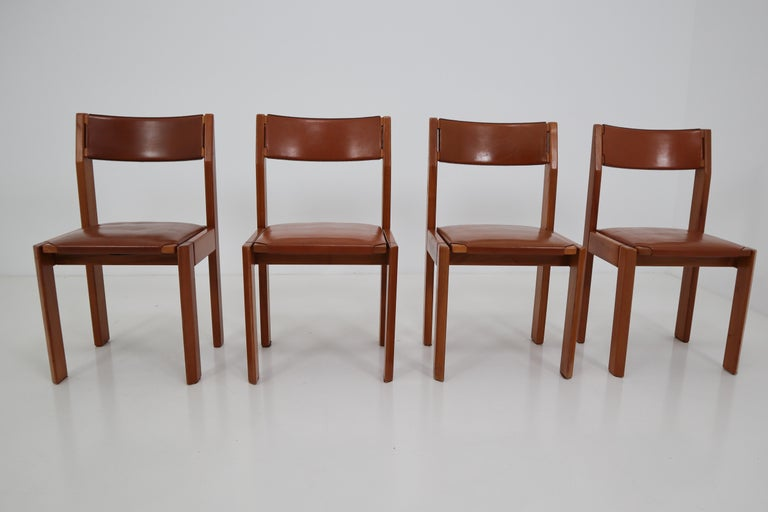 Set of four leather and elmwood dining chairs in the style of Pierre Chapo. Made in France, 1970s.