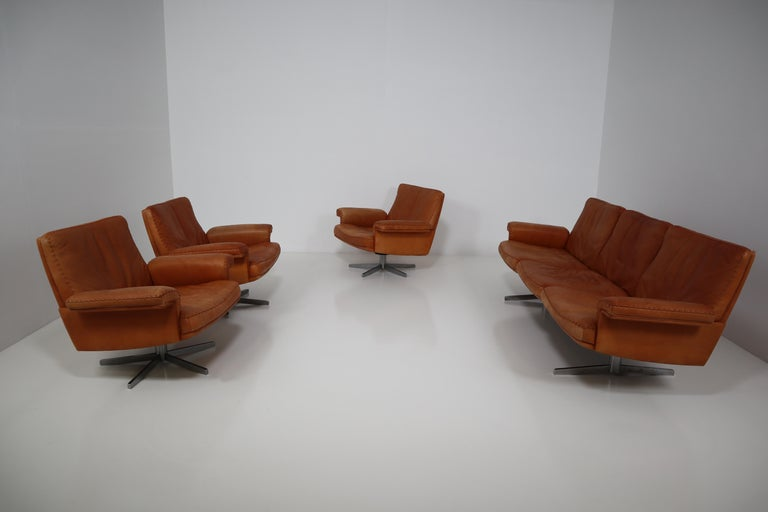 De Sede DS 35 swivel lounge armchairs and three-seat sofa is upholstered in cognac aniline leather with a whipstitch edge detail. It was manufactured in the late 1960s by De Sede from Switzerland. This swivel lounge armchairs and sofa stands on
