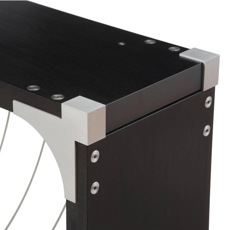 Divergence's exposed aluminum corner bracket perfectly combines function and elegance. The table features two bold swaths of cable which cross in a dynamic fan. The cables flex as they are touched, yet fall back into their fan-like position when