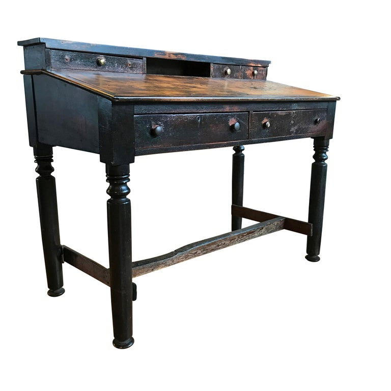 An early 20th century American factory foreman's desk with a slant top, three small drawers on top, and two large drawers below. The wear on the stretchers is remarkable, and clearly shows that the foreman stood on the left of the table for many