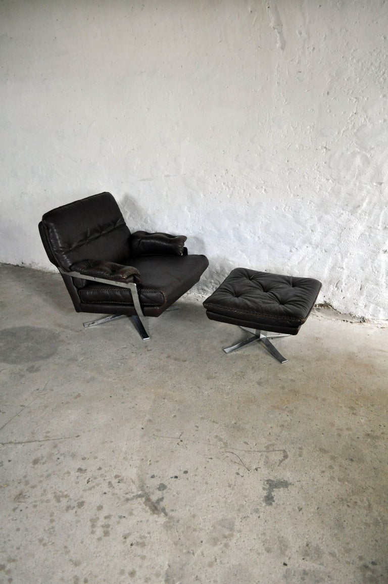 Dark brown leather and chrome lounge chair and stool by Arne Norell. High quality hand-stitched leather and chrome. Very fine vintage condition. Two and three-seat sofa and high back chair also available. Ref: LU3745110874333, LU3745110874373 and