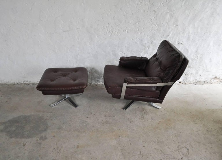 Reddish brown leather and chrome lounge chair and stool by Arne Norell. High quality hand-stitched leather and chrome. Very fine vintage condition. Two and three-seat sofa also available.
