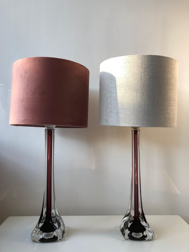 A pair of elegant Swedish Mid-Century Modern Sommerso style table lamps in hour glass form. Two tone glass in burgundy and clear glass inMurano Sommerso style. Pieces of art glass!  Design by Swedish Flygsfors' Paul Kedelv and part of his
