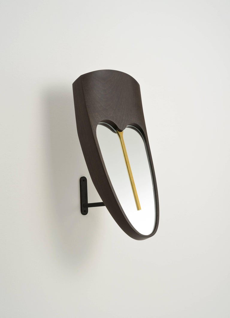A functional mirror for a dressing room, or wooden masks and sculpture for your living or your entrance. The forehead mask Eze, is made of solid beech wood Wengè finishing, with a brass element on the mirror. The base is an iron stand black