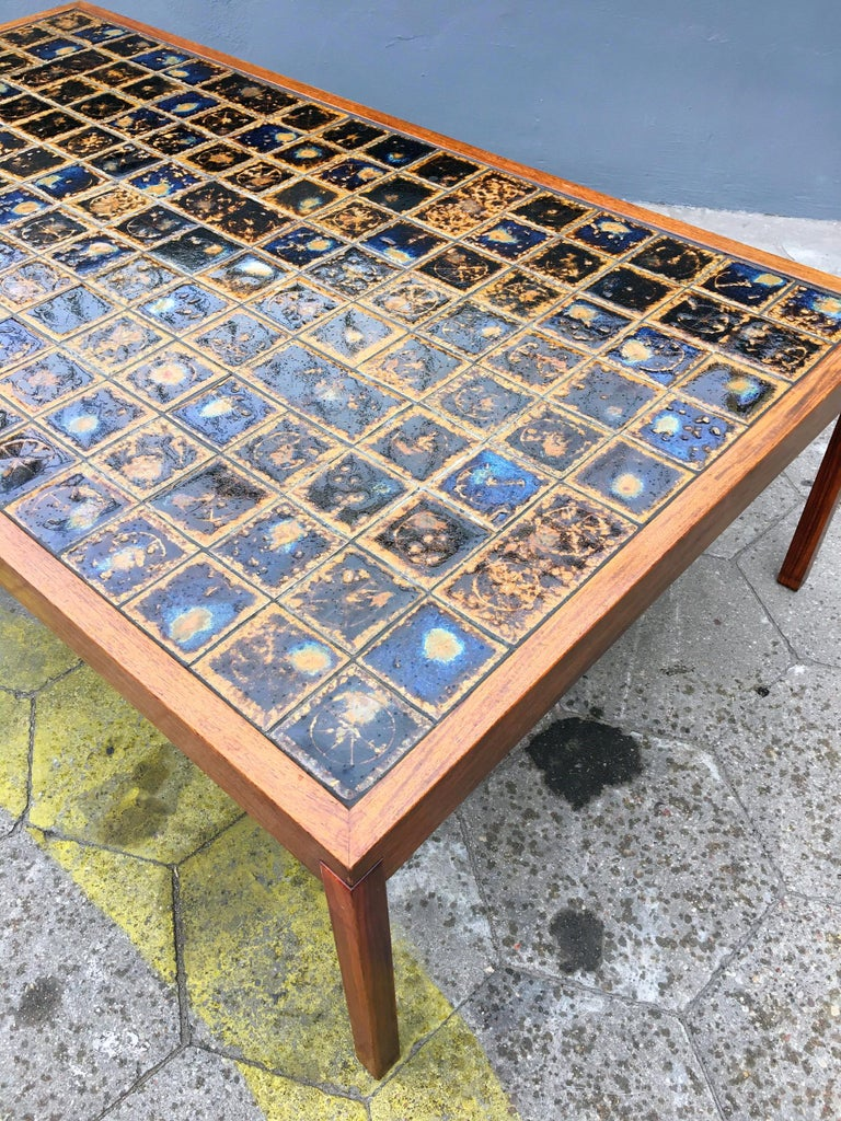This Danish teak wood coffee table was made in 1960s, which has no influence on his condition, which I would call ideal. The wooden surfaces are intact, also the top made of opal-colored, dark blue ceramic tiles is in perfect condition. The only
