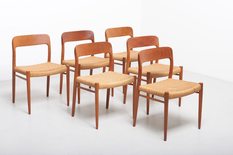 Set of six dining chairs in teak with carved seat backs. Design by Niels O. Møller in 1954. Made by J.L. Møllers Møbelfabrik in Denmark. Set includes six model 75 side chairs with new papercord seats.