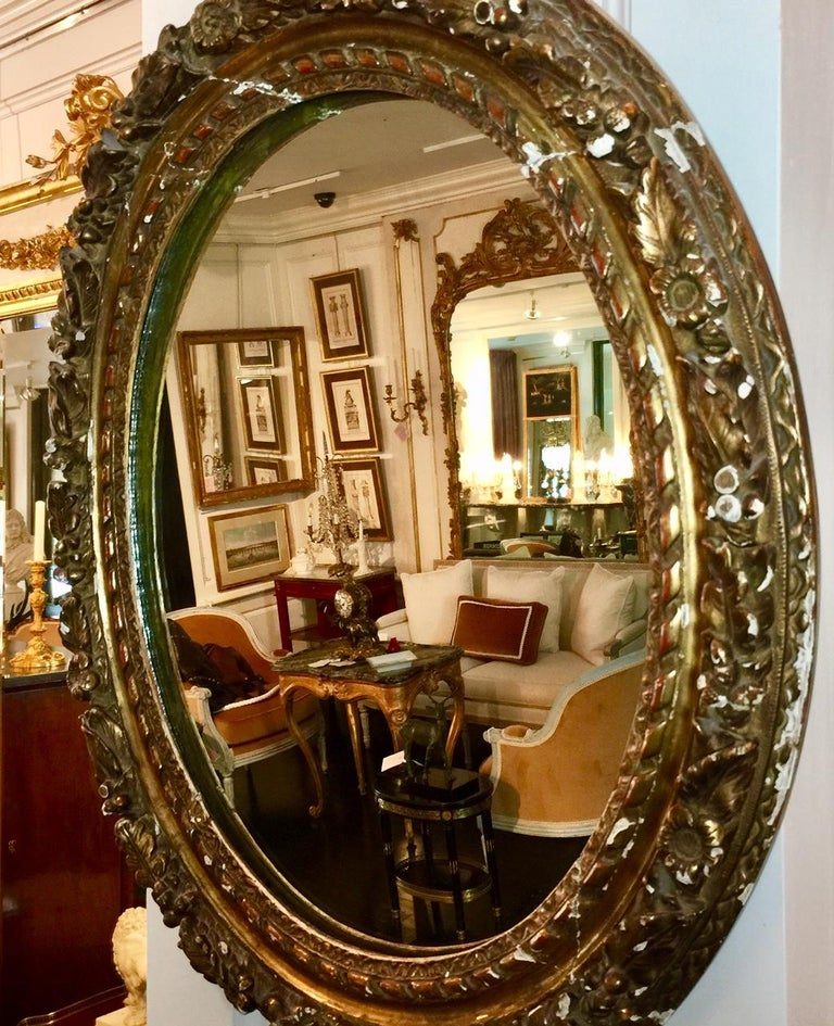 French, neoclassic style. This antique French Louis XVI period, 18th century beveled mirror features a beautifully ornate carved gilt leaf wood frame with flowers, berries and leaves. The oval frame surrounds the original beveled mirror glass which