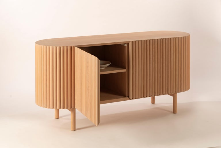 Between the sculpture and the functionality of the object, the RIMA credenza is inspired by the dynamism and the cadence of a poem, drawing all the attention to the wooden slats that are repeated one after the other to form a texture that embraces