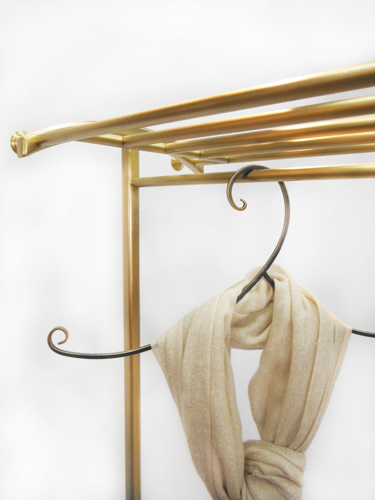 Beautifully handcrafted by artisans from solid architectural bronze. Removable wheels add flexibility and functionality. Aesthetically proportional curvature adds elegance to the piece. This clothing rack is perfect for coats and can hold shoes as