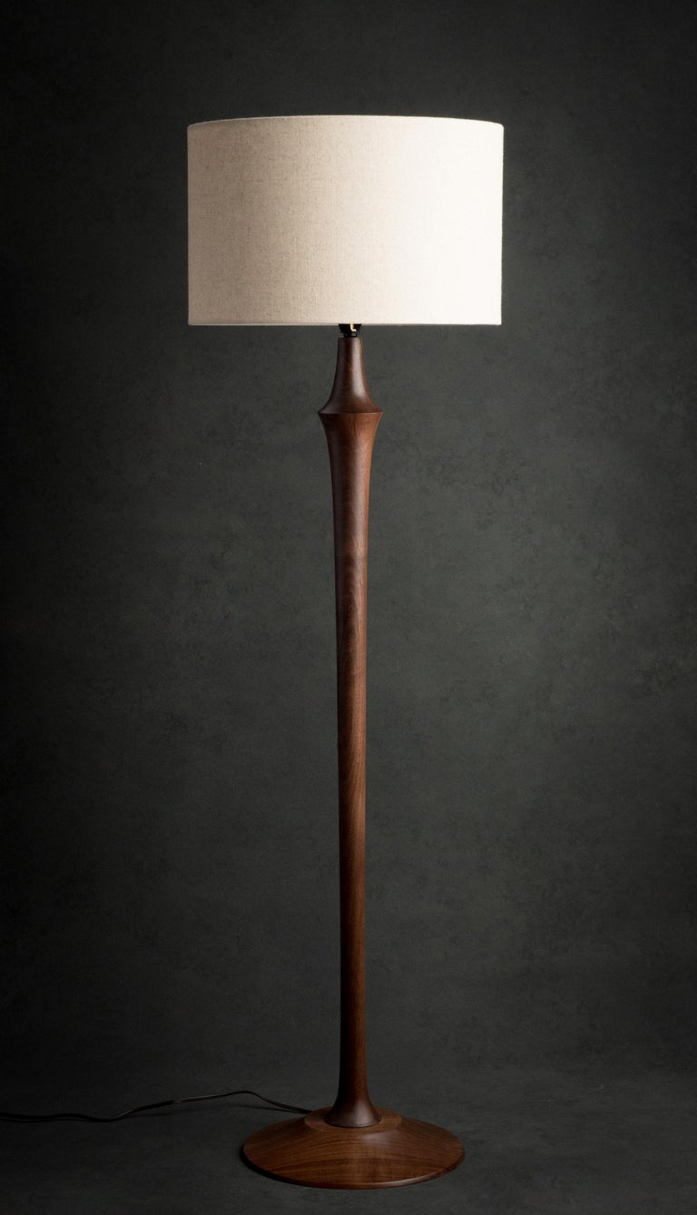 The Guthrie floor lamp is hand-turned on the lathe and can be made out of walnut, cherry, or ash. It features a brass socket, ferrule, and finial and a brown cord. Fabric cords are an option.   The lamp (not including the shade) is 43