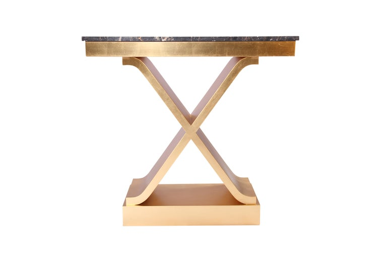 Contemporary gold leaf, gilded and hand finished console table with a wooden frame and a black marble top.