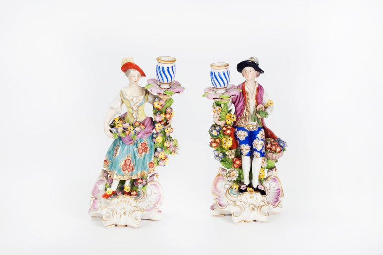 Pair of candlesticks featuring a woman and a man each holding a candlestick surrounded by flower garlands, gilded on the rims overall hand-painted patterns and base decorated with shells in Rococo style.   Measures: Height 27 cm.