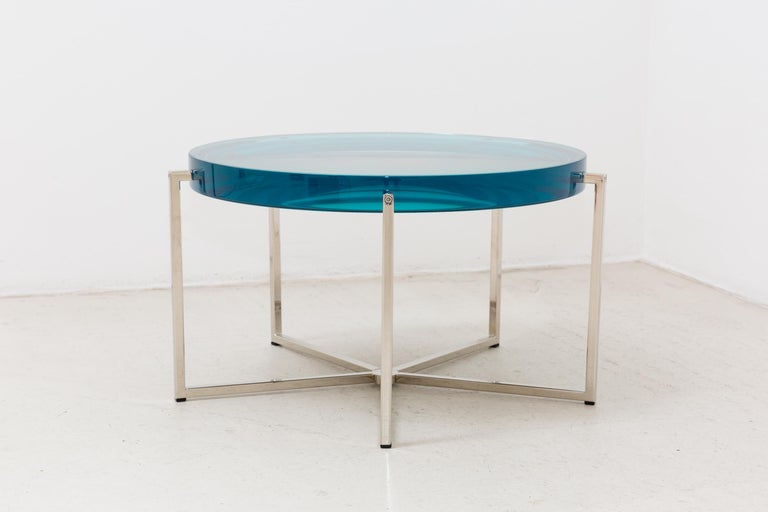 McCollin Bryan Lens table ins turquoise. Resin top backed by acrylic mirror on nickel base with five legs.