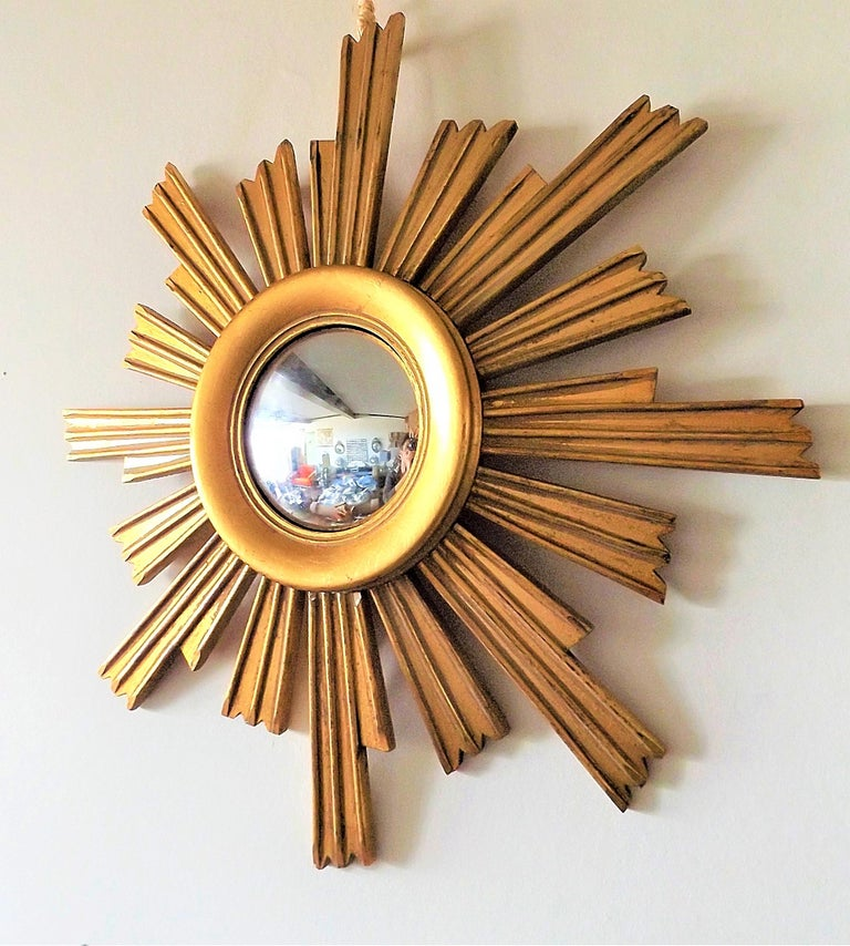 Vintage wooden sunburst mirror with convex glass.