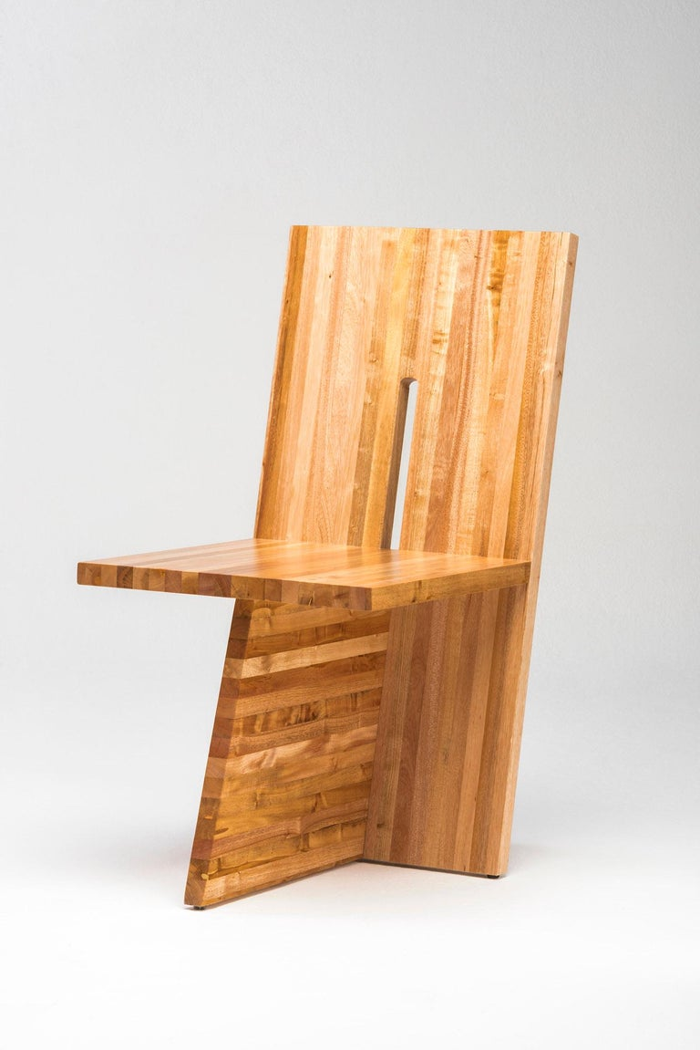 Contemporary chair by Juliana Lima Vasconcellos made in Solid African mahogany wood panel, with and architectural aesthetic formed by embedded planes that create an image of simplicity and balance.