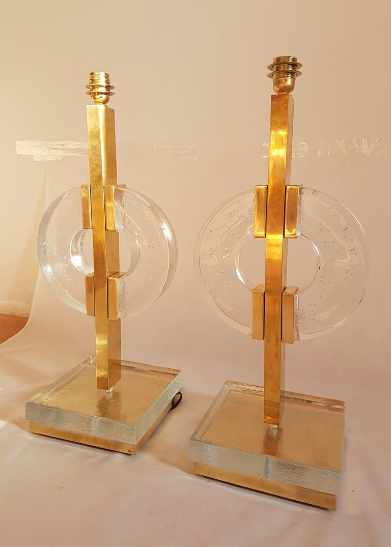 Large pair of Mid-Century Modern Italian table lamps, circa 1960s. Made of brass and very thick clear Murano glass, with air bubbles inside. They have been rewired for the US: 1 medium base bulb each. Sold as a pair, without shades. In excellent