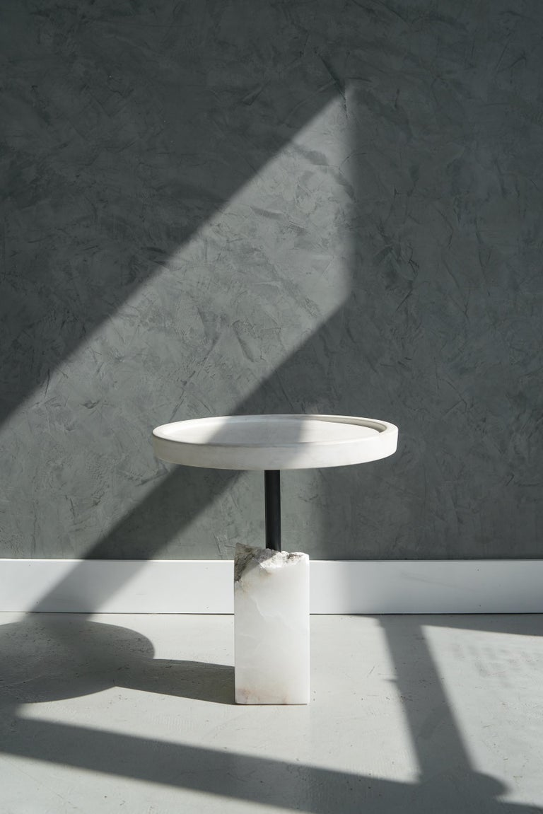 Bleached maple top above a fragmented chunk of alabaster supported by a blackened steel pipe make up this side table.