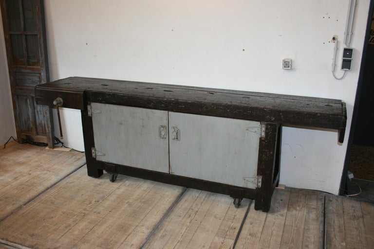 Massive old industrial oak workbench from an old factory in Belgium. This special workbench is movable on four original old industrial rollers and has below two doors, which have been retrofitted over the decades, behind which are shelves. ready