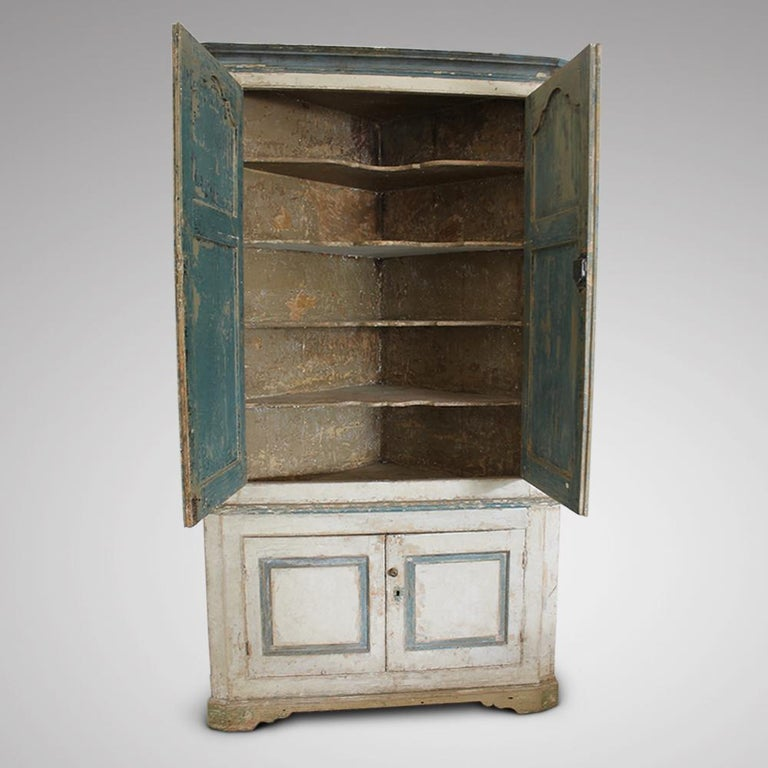 A truly wonderful, English, George III, floor standing pine corner cupboard. Dry scraped back creatively to early layers of off white and blue paint, with large shaped interior shelves and deep moulded panels. In very good condition, a couple of