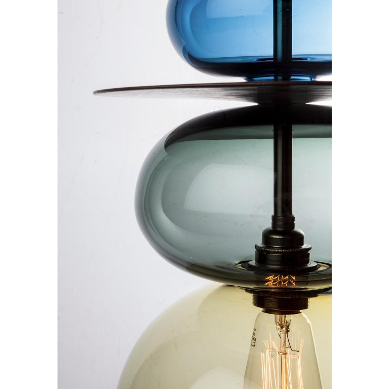 The Triptych Orb is a contemporary stacked glass and wood pendant light inspired by Asian and Moroccan finials and spires. This large ceiling light can be displayed as a single statement piece or as part of a specially designed Triptych set.