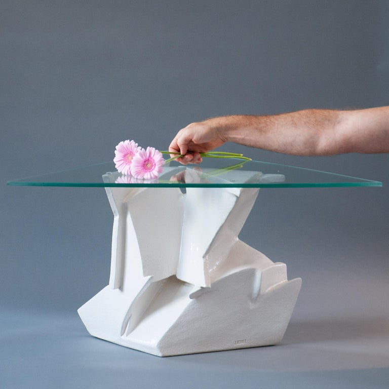 Lines, angles, cutouts, and shadows converge to make a dynamic piece of art. Triangular tempered glass rests on a hand-built base that's folded and molded from glossy stoneware. A beautifully functional one of a kind work. Glass is cut to a hand