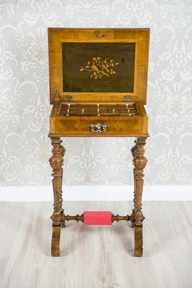 We present you this sewing table that has been made in walnut wood. The piece of furniture is in a rectangular form on two turned, baluster supports which are joint together with a cross bar in a similar style. In the middle of the cross bar,