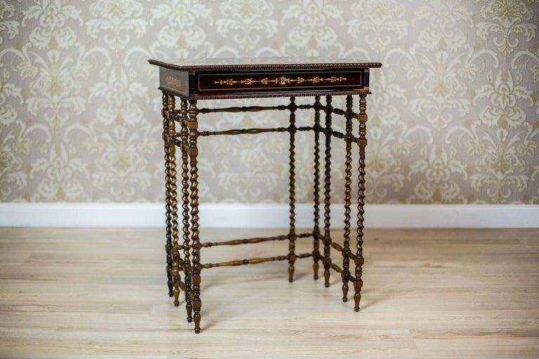 We present you a beautiful sewing table, dated the first half of the 19th century. The rectangular apron is covered in rosewood veneer with beautiful intarsias. Under the top, there is a narrow drawer with a pincushion inside. The whole is