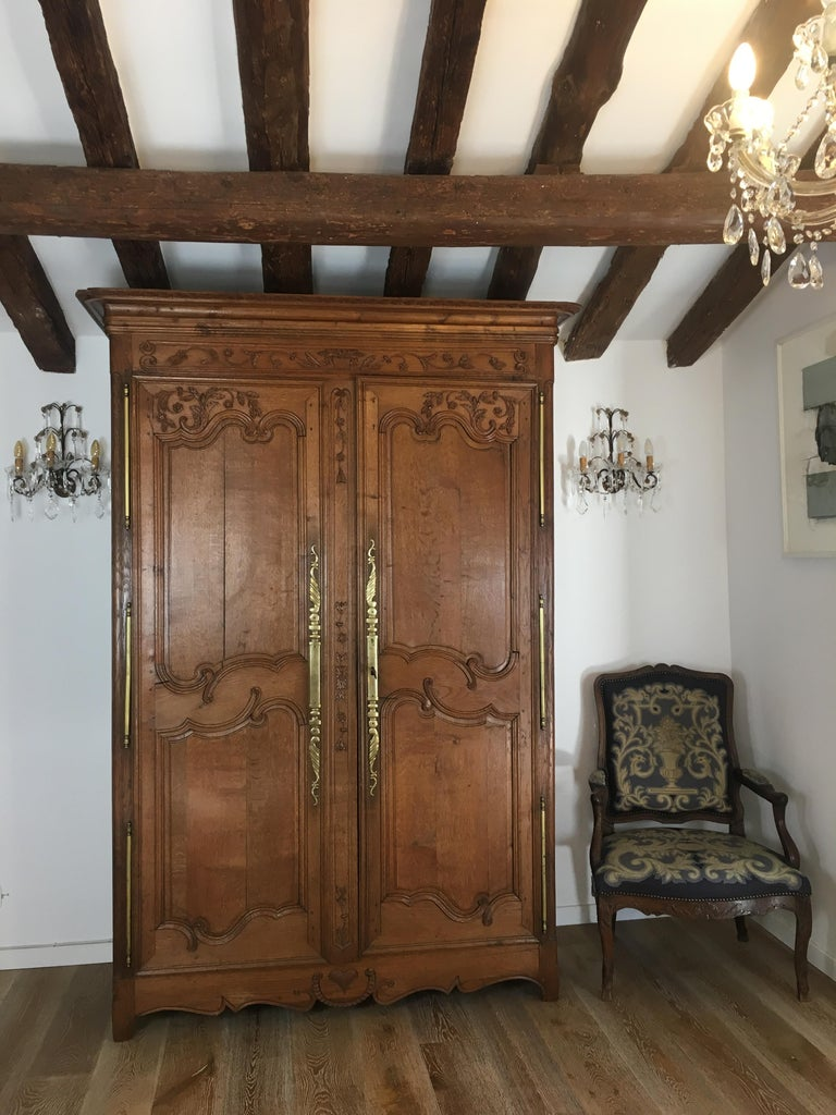 A very good quality carved oak armoire originating from Normandy, France which was made during the early 19th century. The case consists of a carved frieze and panelled doors above a shaped apron. Most notable are the carved door panels and crown