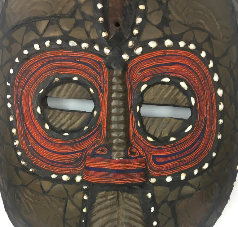 Magnificent African tribal mask hand-carved and constructed with copper and wood. Decorated with elaborate shells, and colorful tribal designs. Very Large and heavy.   Exact origins are unknown, however, this large decorative piece resembles