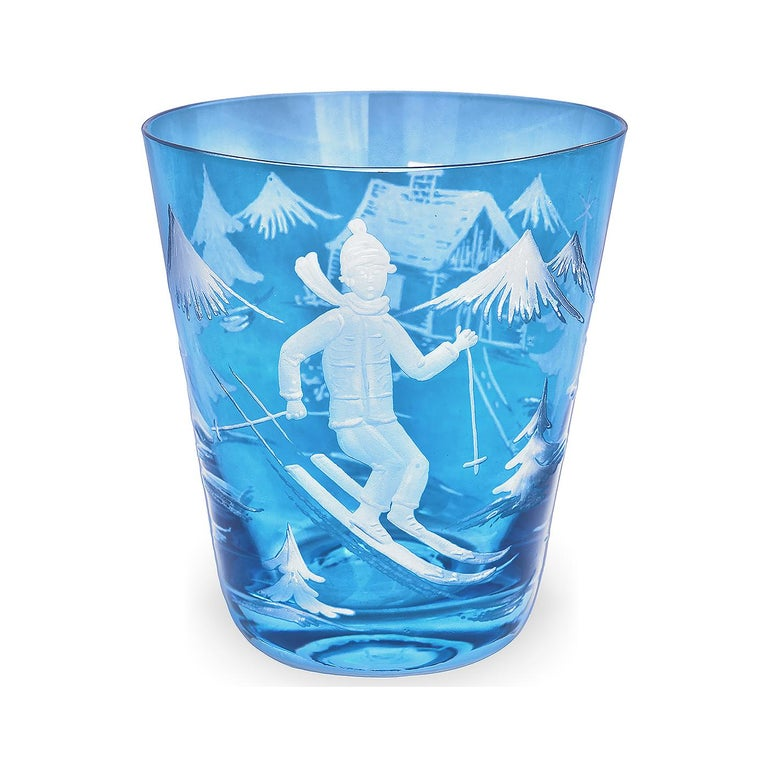 Set of six hand blown tumbler in blue crystal with a hand-edged skier decor. The decor is a modern scene, showing a skier boy, trees and mountains and a chalet all-over the glass. A matching crystal carafe can be ordered in addition.