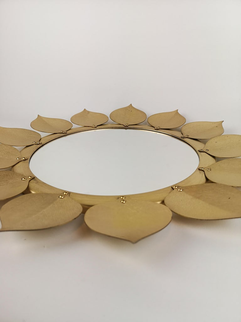 Mirror made in Sweden Västerås in the 1960s. Metal leaves and mirror over glazed in gold colure. Good condition, with some wear and one leaf with some gold lose on the back of the mirror.   Measures: 44 cm diameter.