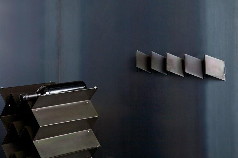 Fold coat rack is a brutalist inspired sculptural wall rack. Made from folded sheet metal with an iridescent zinc plated finish, the intention of the Fold collection is to express the purity of manufacturing processes and materials. This version of