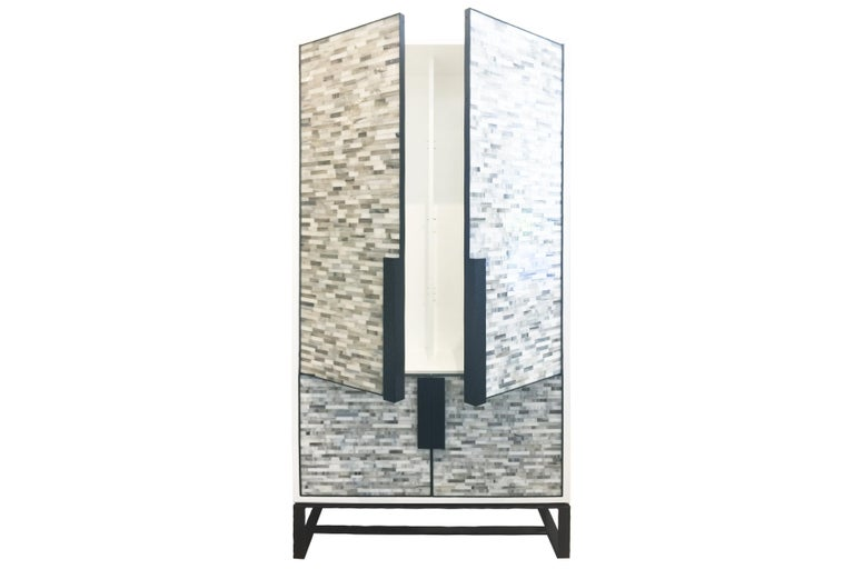 The Chelsea bar cabinet by Ercole Home has a 4-door front, with white lacquer wood finish on oak. Hand cut glass mosaics in London grey and icy white decorate the surface in Luis pattern. Hand-hammered metal framed doors, handles, and base in