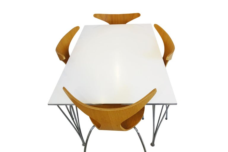 A Mid century 1960s designed white and silver rectangular dining table designed by Piet Hein, Arne Jacobsen and Bruno Mathsson manufactured by Fritz Hansen in 1989 and a set of Danish designed Danform 'Dolphin' stacking chairs in oak veneer and