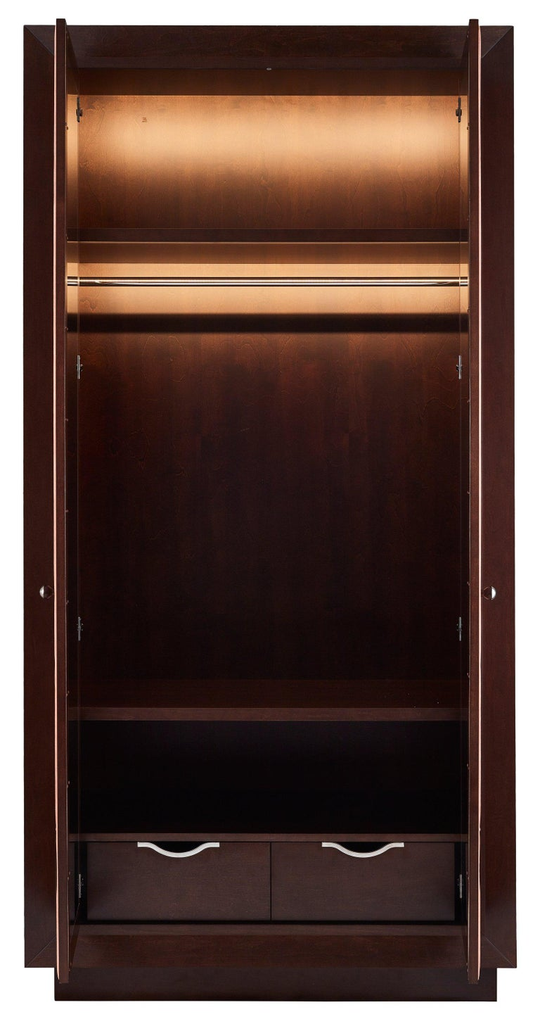 The high wardrobe is finished in fine tinted sycamore veneer and salmon Alcantara on door panels. The panels are decorated with the pattern of chrome-plated studs. The fern-like poetic pattern brings here the magic of enchanted forests. The