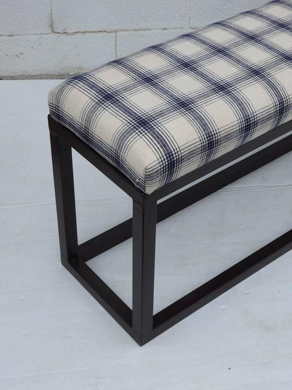 Long narrow bench with iron base and upholstered seat with in French vintage check fabric.