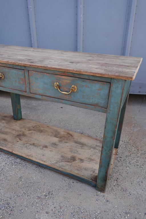 Long painted dresser base or serving table with four drawers. Natural pinewood top. Old blue green paint remains. Original brass hardware. (Depth needs to be confirmed).
