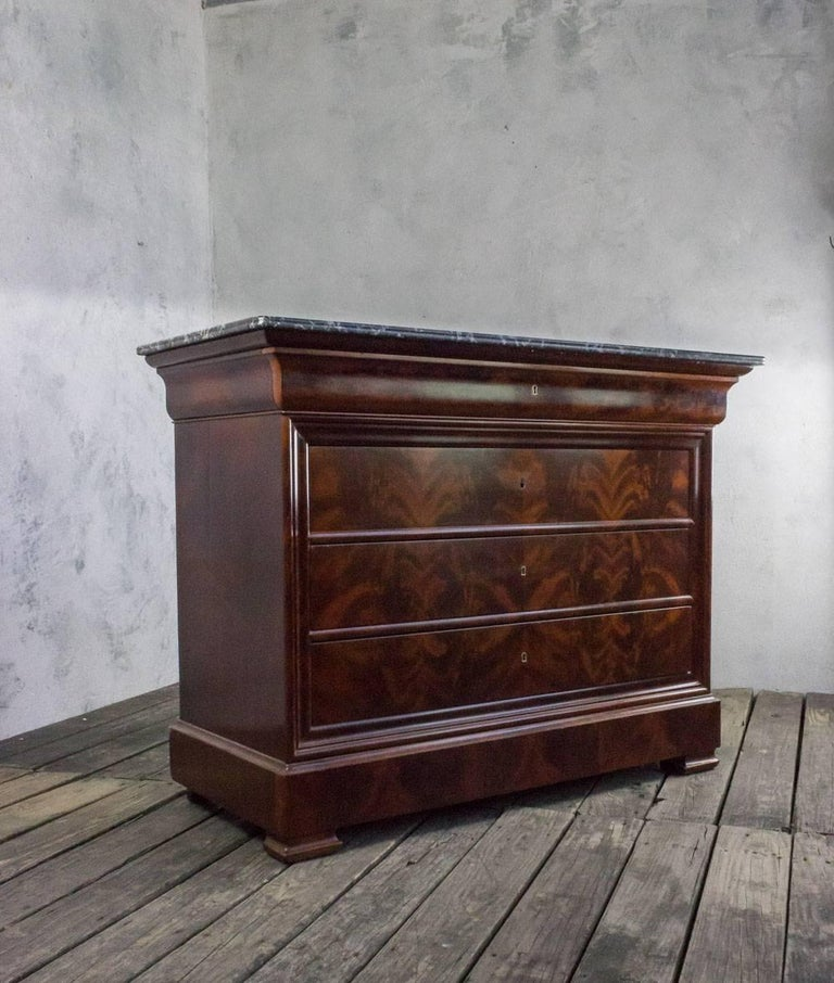 Flame mahogany veneered Louis Philippe chest of drawers with original gray marble and five drawers. Original keys and locks. This piece is in good conditions, sold in